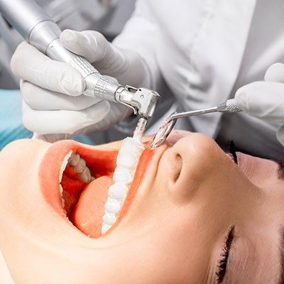 Female getting prophylaxis, also known as a teeth cleaning
