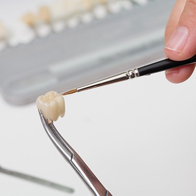 A periodontist preparing a crown for crown lengthening